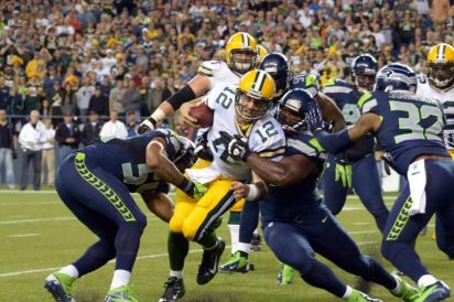 Aaron Rodgers busts his way through the sound Seahawks defence - Photo Courtesy of iSportsweb